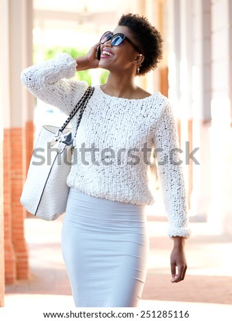 Portrait of a happy african american woman walking outdoors with mobile phone - stock photo