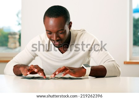 Portrait of a happy african man sitting on the table with bills of US dollars - stock photo