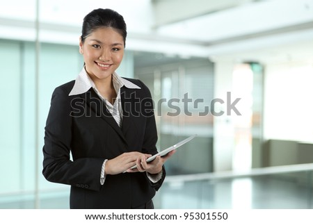 Portrait of a happy Asian business woman using a tablet PC. - stock photo