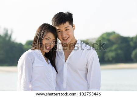Portrait of a happy Asian couple on the beach.