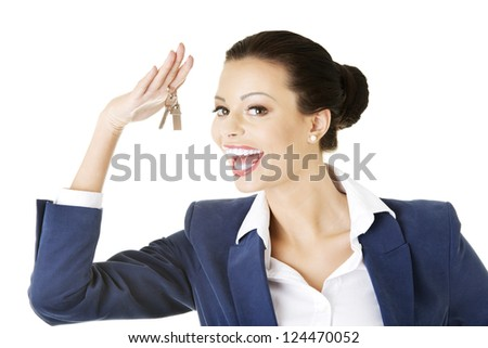 Portrait of a happy attractive caucasian businesswoman, real estate agent, holding a house key against a white background - stock photo