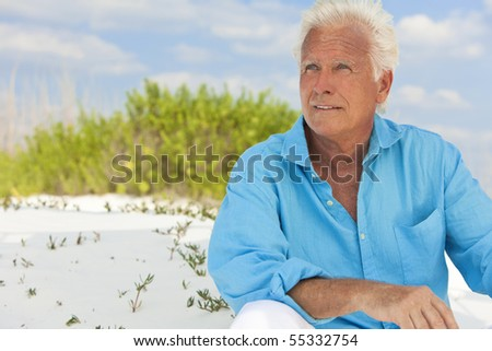 Portrait of a happy attractive handsome senior man sitting down outside on a white sand beach - stock photo