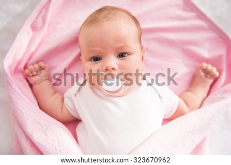Portrait of a happy baby lying on the bed at home