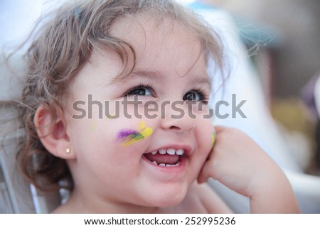 portrait of a happy baby with paint in the face - stock photo