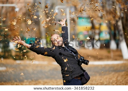 Portrait of a happy bald man photographer with professional digital camera on his neck, he throws tons of leaves falling in the air in autumn park, enjoying the sunshine weather, glad and satisfied.  - stock photo