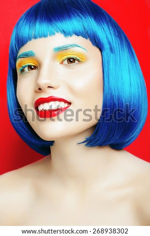 Portrait of a happy beautiful girl with blue hair and manicure in the studio on a red background, the concept of health and beauty - stock photo