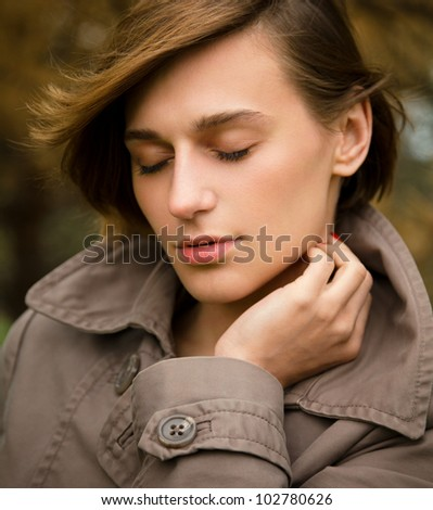 Portrait of a happy beautiful woman in autumn park, pale colors - stock photo