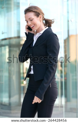 Portrait of a happy business woman talking on cell phone outside - stock photo