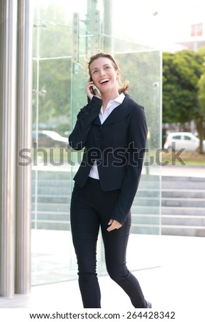 Portrait of a happy business woman walking and talking on cell phone - stock photo