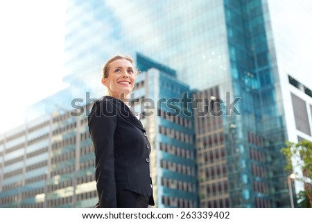 Portrait of a happy business woman walking outside in the city - stock photo