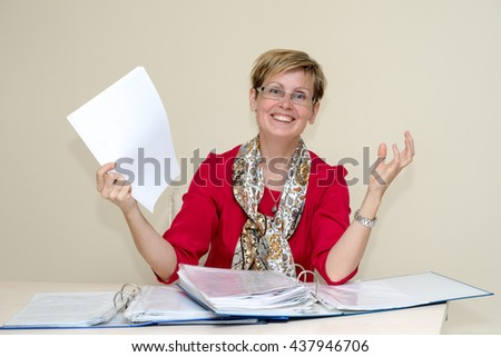 portrait of a happy business woman with papers sitting on the desk and holding up a paper sheets - stock photo