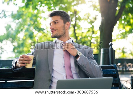 Portrait of a happy businessman sitting on the bench with laptop and drinking coffee outdoors. Looking away - stock photo