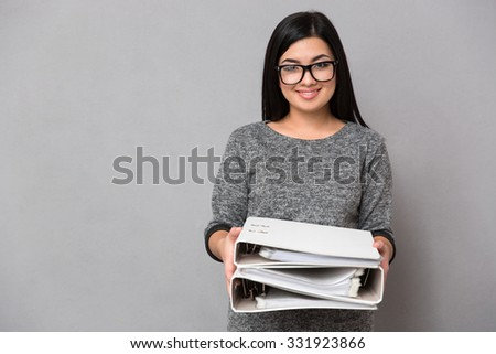 Portrait of a happy businesswoman holding folders over gray background - stock photo