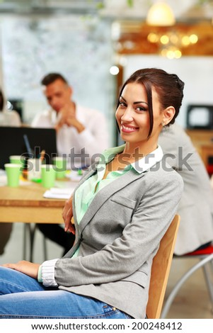Portrait of a happy businesswoman in front of colleagues