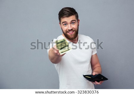 Portrait of a happy casual man giving money at camera over gray background - stock photo