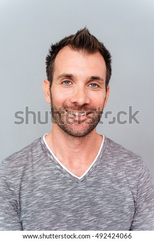 Portrait of a happy casual man over gray background