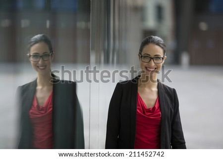 Portrait of a happy caucasian business woman leaning against a window. - stock photo