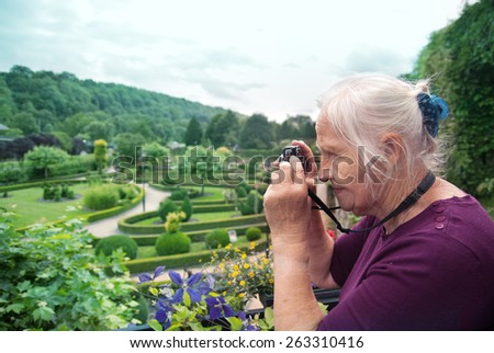 Portrait of a happy caucasian senior woman taking photo in a park. Active retirement - stock photo
