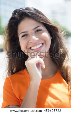 Portrait of a happy caucasian woman in a orange shirt in the city - stock photo