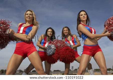Portrait of a happy cheerleader cheering with friends in the background - stock photo