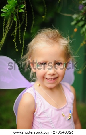 Portrait of a happy child, cute adorable little girl in a fairy costume with fairy wings on her birthday - stock photo