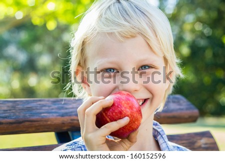 Portrait of a happy child eating a red apple outdoors. - stock photo