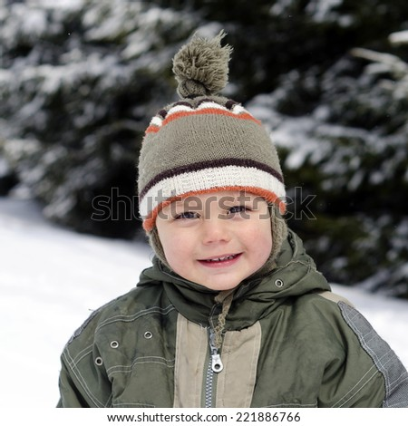 Portrait of a happy child in winter snow.  - stock photo