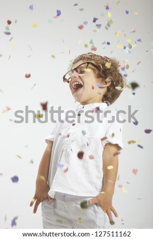 Portrait of a happy child wrapped with confetti - stock photo
