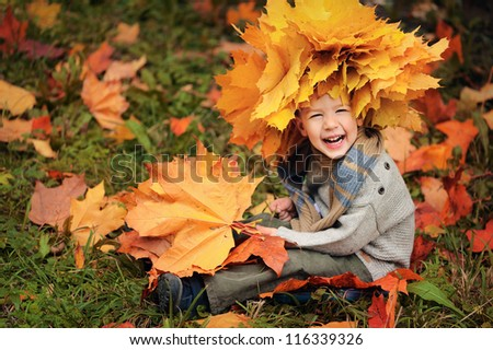 portrait of a happy child. Wreath of yellow leaves on head