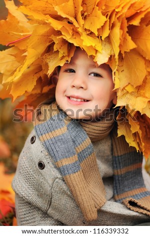 portrait of a happy child. Wreath of yellow leaves on head - stock photo