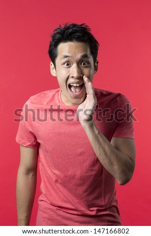 Portrait of a happy Chinese/Asian man shouting. Red background. - stock photo