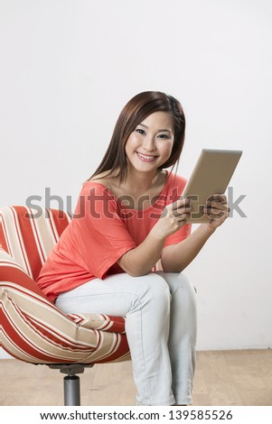 Portrait of a happy Chinese woman sitting on a chair using Digital Tablet