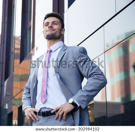 Portrait of a happy confident businessman in suit standing outdoors  - stock photo