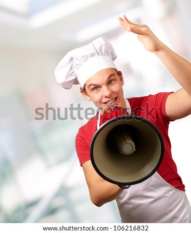 portrait of a happy cook man shouting using a megaphone indoor