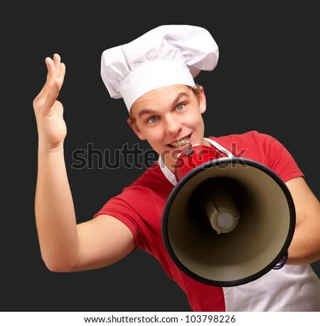 portrait of a happy cook man shouting using a megaphone over a black background
