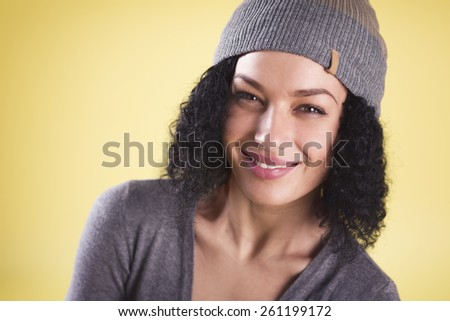 Portrait of a happy cool woman smiling and representing young generation isolated on yellow background with empty copy space. - stock photo