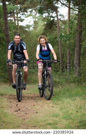 Portrait of a happy couple cycling in nature - stock photo