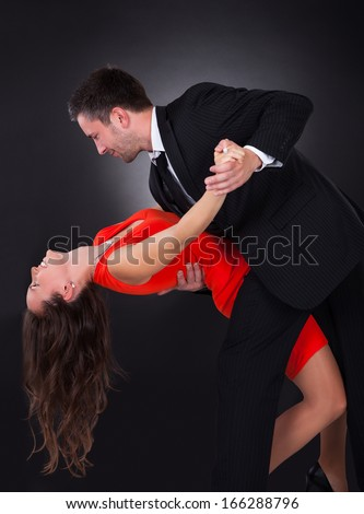 Portrait Of A Happy Couple Dancing On Black Background - stock photo
