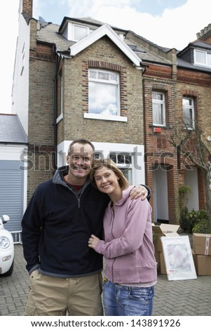 Portrait of a happy couple embracing in front of house - stock photo