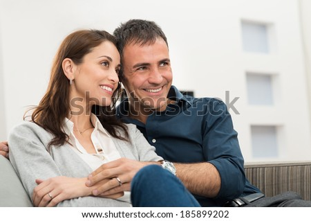 Portrait Of A Happy Couple Embracing Sitting On Couch - stock photo