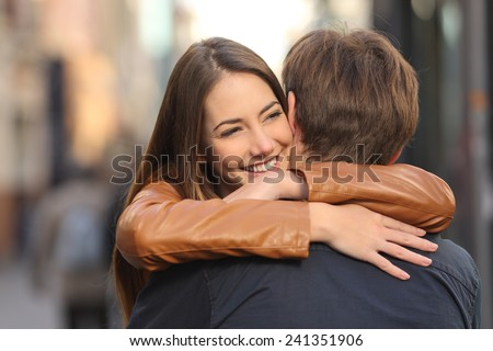 Portrait of a happy couple hugging in the street with the woman face in foreground - stock photo