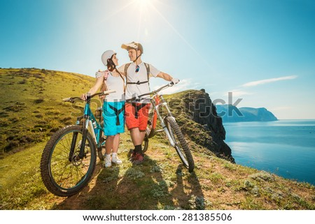 Portrait of a happy couple in the mountains with bicycles. Young man and woman traveling on mountain bikes outdoors.