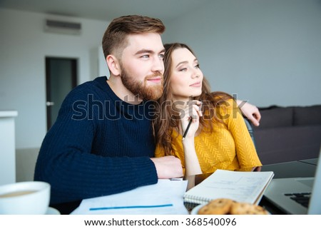 Portrait of a happy couple sitting at the table with bills and looking away - stock photo