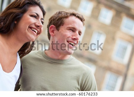 Portrait of a happy couple smiling outside their building - stock photo
