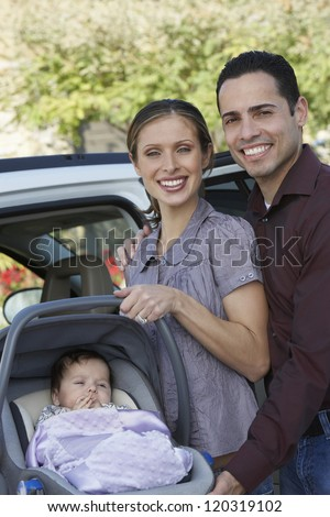 Portrait of a happy couple standing with baby carrier by car