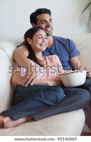 Portrait of a happy couple watching television while eating popcorn in their living room - stock photo