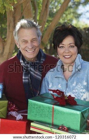 Portrait of a happy couple with gift boxes in lawn