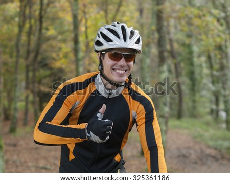 Portrait of a happy cyclist with ok symbol - stock photo