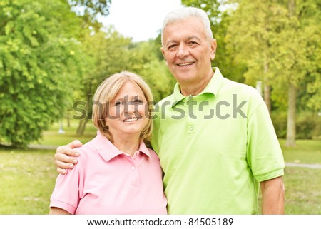 Portrait of a happy elderly couple outside. - stock photo