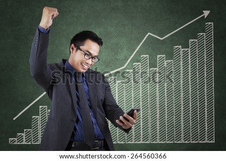 Portrait of a happy entrepreneur reading a message while expressing success near the business growth chart - stock photo